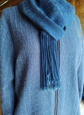 """Jan M - Jacket & scarf. Jacket is woven in 2-shaft plain weave using indigo-dyed 5/2 cotton and 3/2 Tencel, and Tahki """"Ripple"""" yarn, sett at 12 epi. Scarf is woven in 8-shaft block twill, using indigo-dyed 10/2 Tencel, sett at 28 epi."""