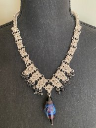 Bev A - Chainmaille necklace in 4-square weave and box chain weave. The piece is made with over 900 5.4 mm 18-gauge silver coated jumbo rings, one-of-a-kind glass focal bead with diamond chips, nd 12 teardrop glass beads.