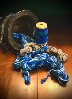 """Chris M - Two handpainted and tan merino braids spun during 2021 """"Tour de Fleece."""" There's also a bobbin with some of the blue fiber behind the braids."""