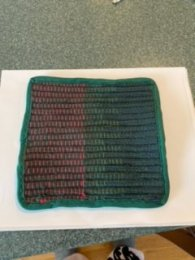 Elizabeth Q - Potholder made from the rug shown elsewhere in this gallery, made with rug warp, sheet strips, and cotton knot rag coils. She's still experimenting with binding the edges but hopes to turn these into holiday gifts. Great way to rescue a project that didn't turn out as expected!